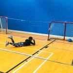 Mini-goalball Saint-Jérôme. Automne 2019. Lili-Rose étendue sur le ventre, regarde le ballon qu'elle n'a pas pu arrêter et qui est dans le but.