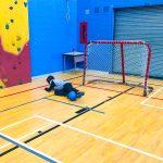Mini-goalball Saint-Jérôme. Automne 2019. Samuel fait l'arrêt du ballon avec ses jambes, étendu sur le côté droit.