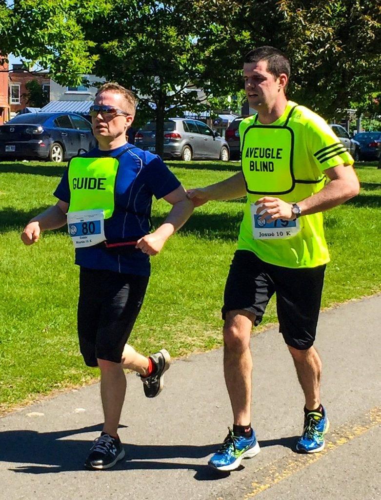 Un coureur aveugle (Josué) et son guide (Martin) courent les derniers mètres du parcours de la course.