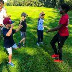 Programme DSPM Montréal-Athlétisme. Harmine montre aux garçons comment bien bouger les bras pour la course.