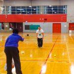 Tennis sonore ASAQ Aut. 2019. La bénévole Neima, vue de dos, lance une balle noire à Dimitri qui est en face.