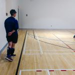 Goalball récréatif ASAQ Aut. 2019. La joueuse Sabrina, vue de dos, se tient le long du terrain pendant une partie.