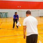 Tennis sonore ASAQ Aut. 2019. Neima lance une balle jaune à Dimitri, qui est vu de dos.