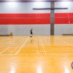 Tennis sonore ASAQ Aut. 2019. Vue de dos de Hugues, Alain et Yan qui s'échauffent face au mur. La bénévole Neima récupère une balle.