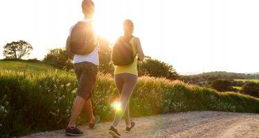 Portrait d'un jeune couple qui marche en plein air sur un chemin de gravier.